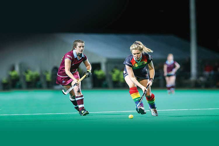 Two hockey players battle for the ball