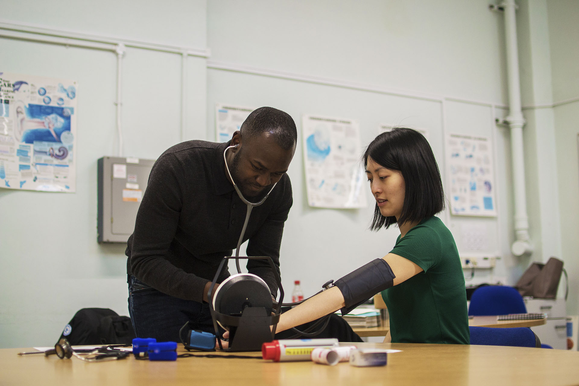 Male student takes female student's blood pressure in a classroom setting